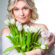 Beautiful woman with spring tulips on gray — Stock Photo
