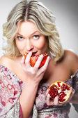 Blonde vrouw granaatappel bijten op grijs — Stockfoto
