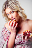 Blonde woman licking pomegranate on grey — Stock Photo