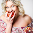 Blonde woman biting pomegranate on gray — Stock Photo