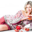Blonde woman with pomegranates lying on isolated white — Stock Photo