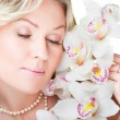Blonde woman with  orchid on isolated white — Stock Photo
