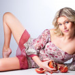 Blonde woman with pomegranates lying on gray — Stock Photo #6324866