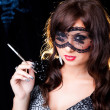 Royalty-Free Stock Photo: Smoking lady with lacy mask on black