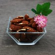 Almond and flowers in the glass square bowl - Stock Photo