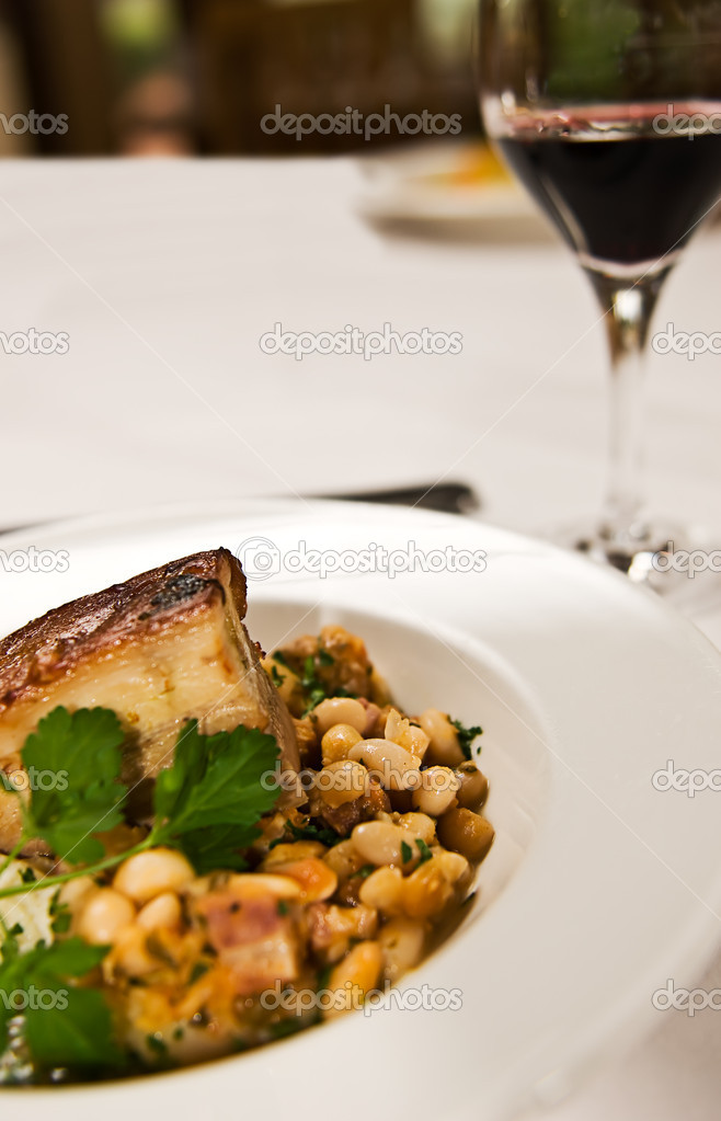 A peice of pork belly served with beans ang a glass of red wine. Restaurant food. — Stock Photo #5540998