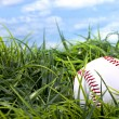 Baseball in grass with blue sky and white clouds — Stock Photo