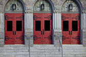 Three red doors in stone building — Stock Photo