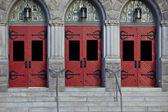 Drei rote türen in steinbau — Stockfoto