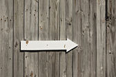 Old weathered wall or fence with wooden arrow sign — Stock Photo