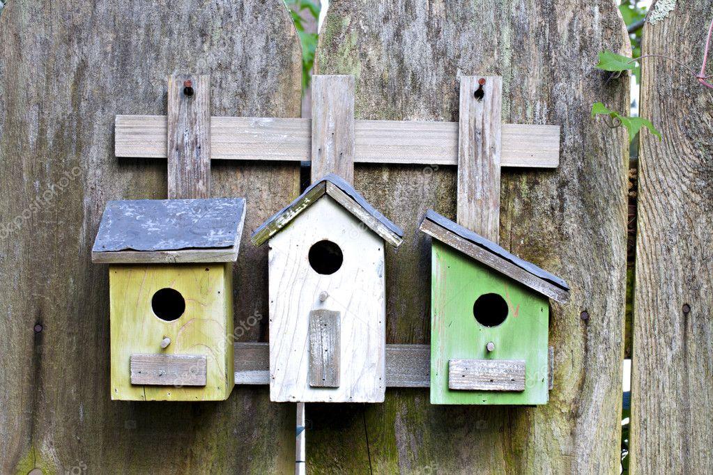 老木栅栏上的三个鸟舍