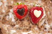 Two strawberries with hearts on a chocolate layer — Stock Photo