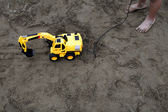 Children playing on the beach remote engineering vehicle — Stock Photo