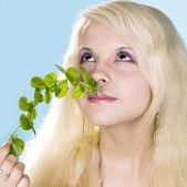 Girl blonde enjoys aroma of mint — Stock Photo