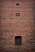 Brick wall with small dark windows — 图库照片