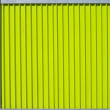 Green-yellow ridged metal fence texture — Stock Photo