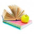 Open book, a stack of notebooks and an apple. — Stock Photo