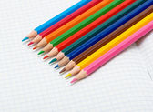 Colored pencils on an open notebook — Stock Photo