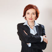 Attractive businesswoman with her arms crossed — Stockfoto