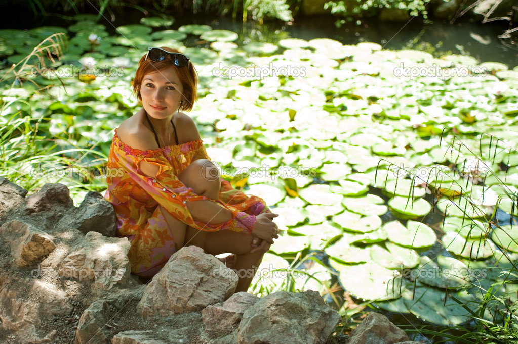Young beautiful woman in a summer hot day resting in the shade by the pond with lilies  Stock Photo #5631126