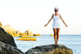 Woman standing on a stone in the sea — Stock Photo
