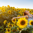 Woman on blooming sunflower field — Stock Photo #6424145