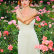 Woman in a garden of roses — Stock Photo