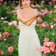 Woman in a garden of roses — Stock Photo #6443113