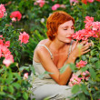 Woman in a garden of roses — Stock Photo #6443153