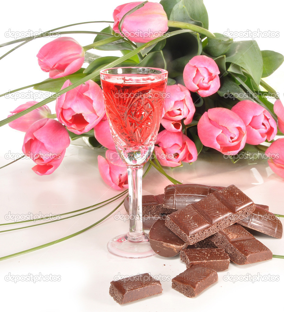 Chocolate, wine-glass of wine and bouquet of tulips lie on a table — Stock Photo #5620687