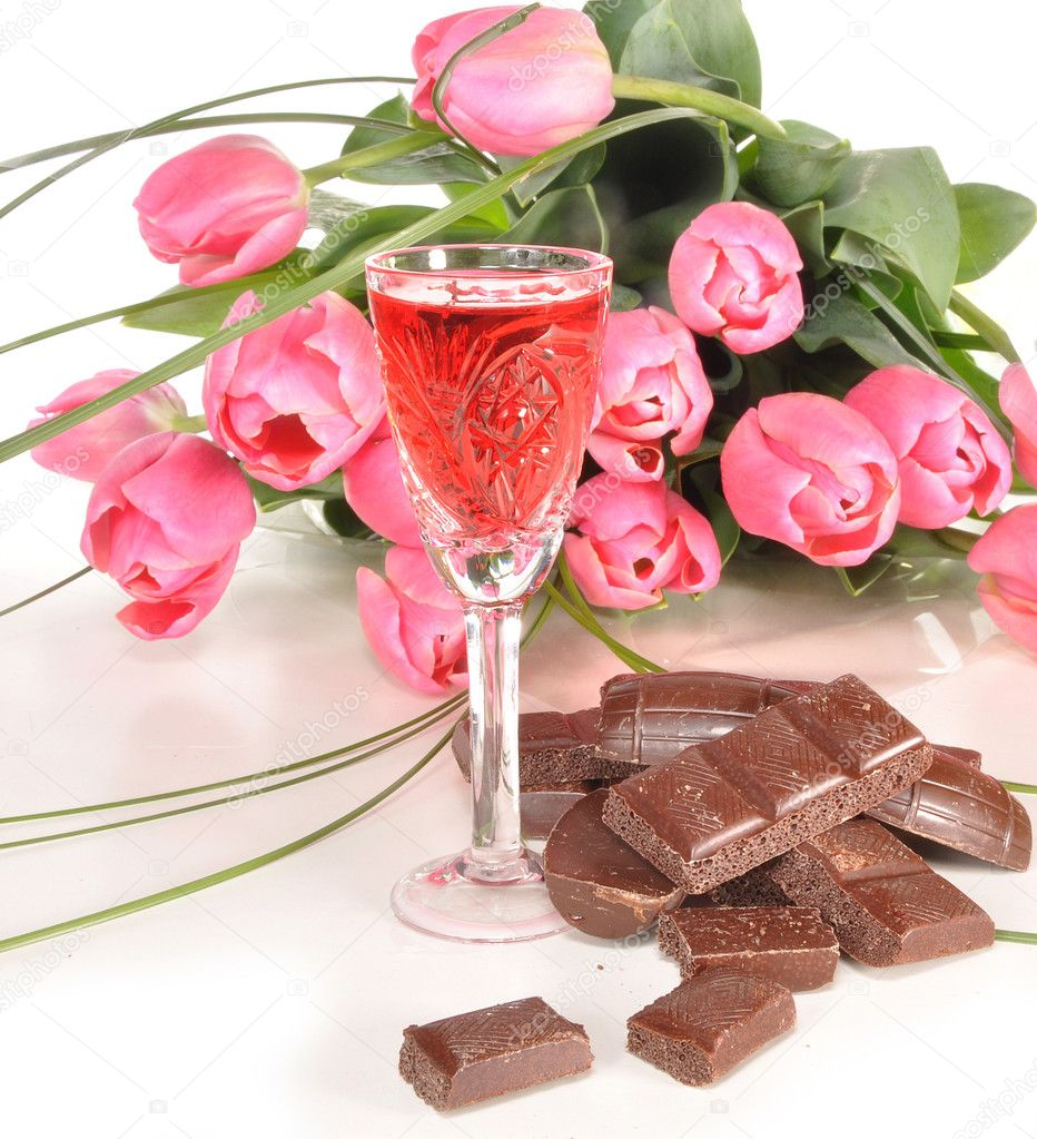 Chocolate, wine-glass of wine and bouquet of tulips lie on a table  Stock Photo #5620687
