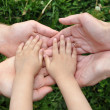 Children&#039;s hands in hands of adults - Stock Photo