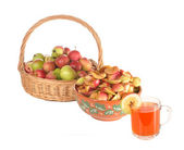 Apples in a basket, slices of apples and a juice glass — Stock Photo