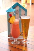Glass of fruit cocktail and a glass of beer — Stock Photo