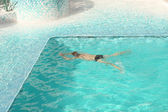 Homem nadando na água azul da piscina — Foto Stock