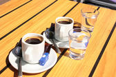 Cups of coffee with a glass of water — Стоковое фото