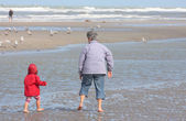 Grandmother and granddaughter walking on the beach with feet in water — Stock Photo