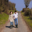 Couple of young walking in the campaign in spring — Stock Photo #6532860