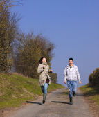 Couple of young walking in the campaign in spring — Fotografia Stock