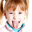 Young girl puting out her tongue - Stock Photo