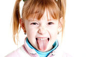 Young girl puting out her tongue — Stock Photo
