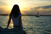Girl sitting near water — Stock Photo
