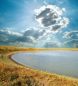 Pond under cloudy sky — Stock Photo