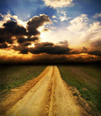 Sunset over dirty road — Stock Photo