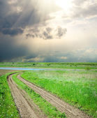Rural road in green grass — Stock Photo