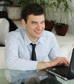 Handsome young men with laptop in public space. businessman smi — Stock Photo