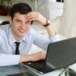 Handsome men think at the laptop - Stock Photo