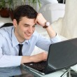 Smiling men think and work at the laptop - Stock Photo