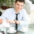 Smiling young men pours tea into a cup — Stock Photo