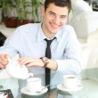Smiling young men pours tea into a cup - Stock Photo